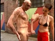 Mistress gives her slave painful handjob out doors