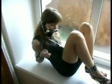 Cuffed and gagged in front of window