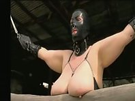 Latex hooded submissive woman punished outdoors