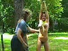 A vintage backyard whipping of buxom woman