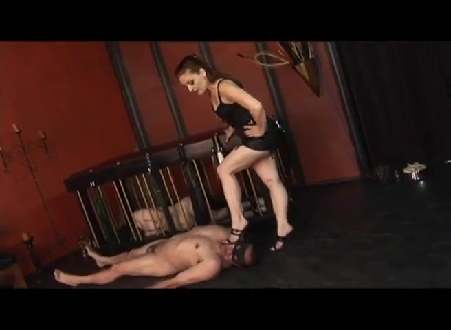 Domme Confines One Naked Male Slave In Cage While Tormenting Other Naked Male